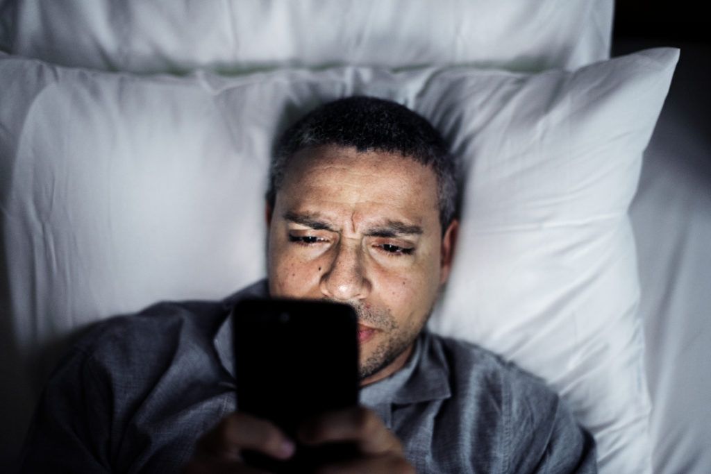 a man with eye strain headache staring at the phone in bed