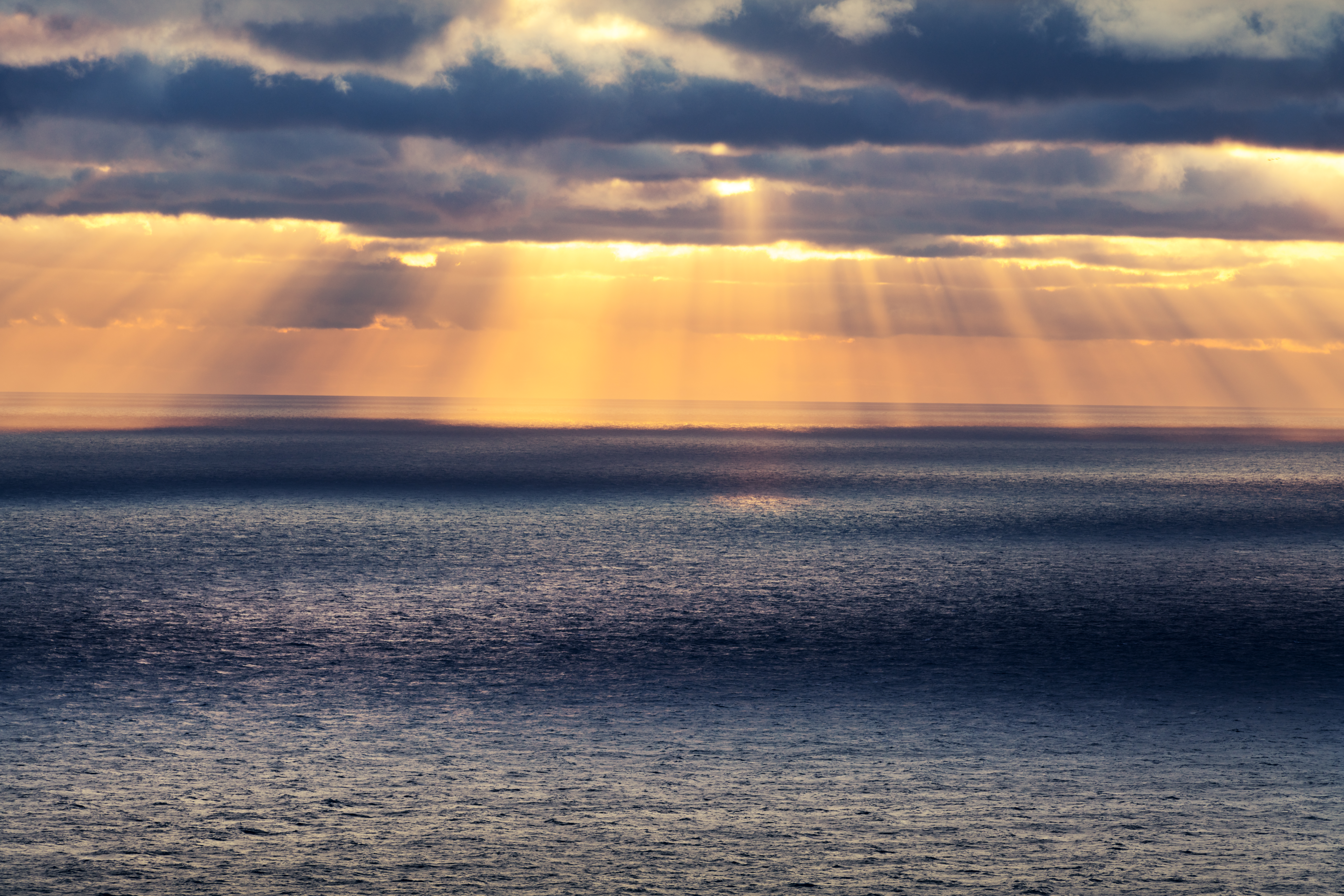sunset in the ocean with glowing sun rays BBZ68CJ - The Science Behind Blue Light