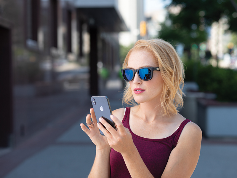 woman protecting eyes with blue blocking sunglasses outside