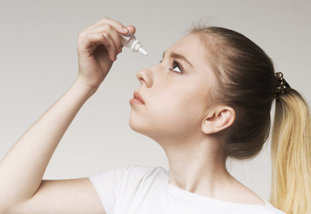 a girl applying a dry eye treatment