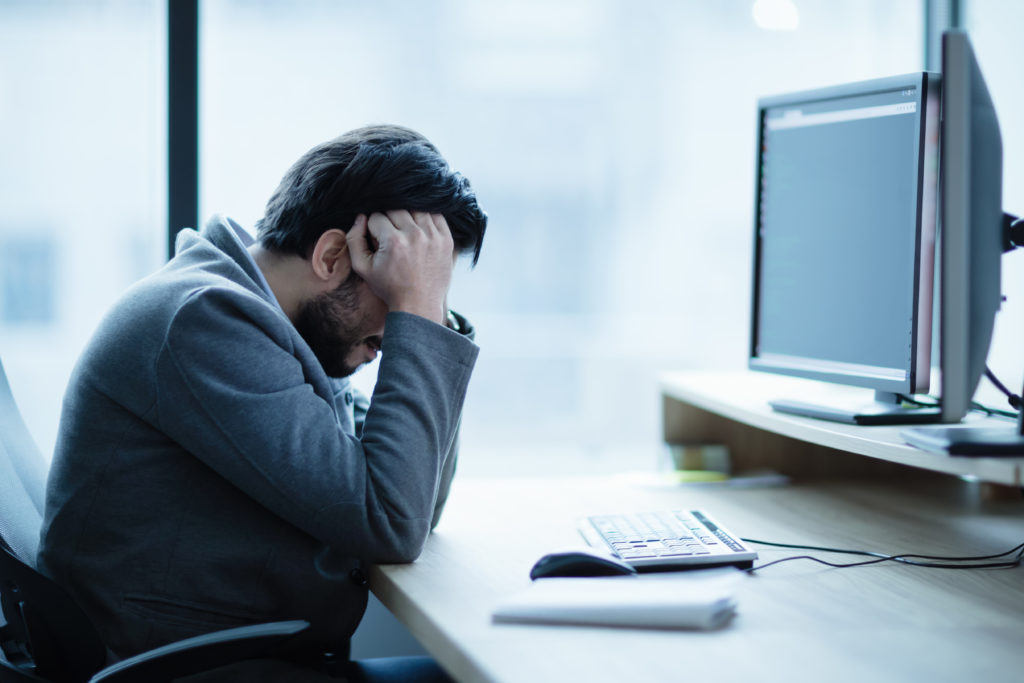 a man sitting experiencing eye strain headache in front of computer