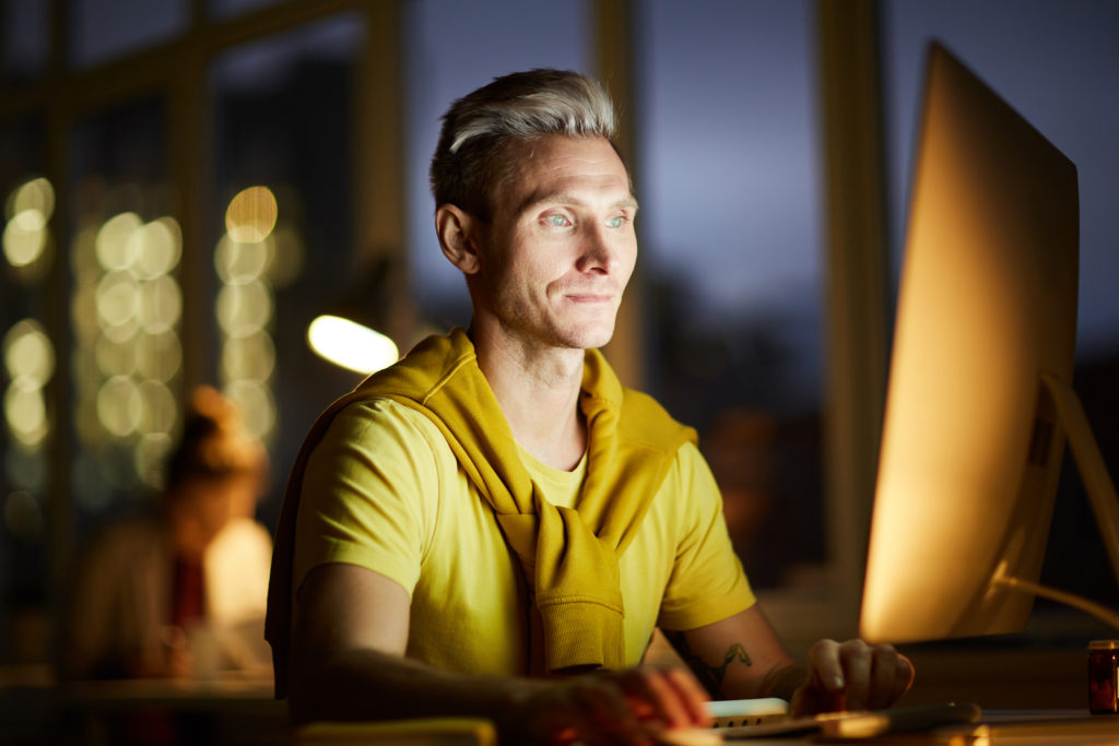 man sitting in front of a computer at night needs blue light protection