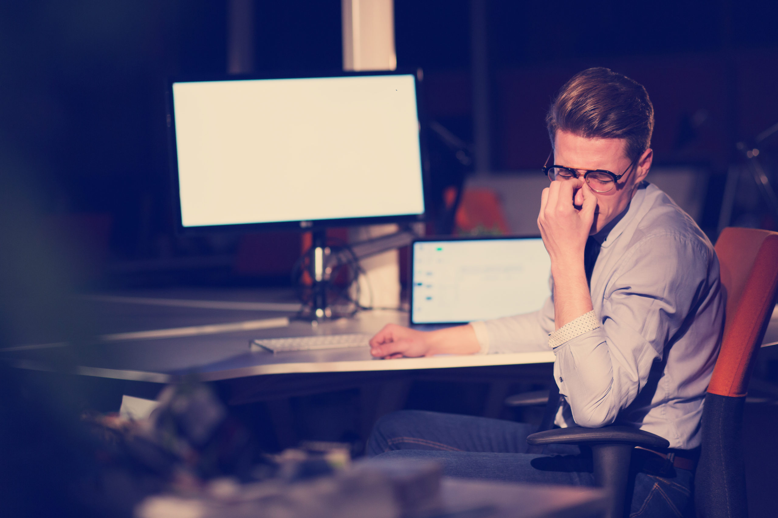 man working on computer in dark office PR8DH5L scaled - What are Sleep Glasses?